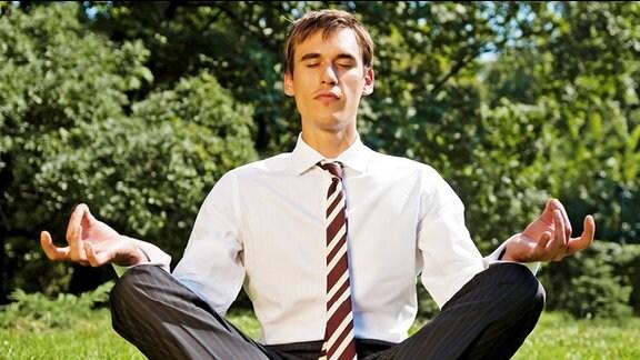 Ein Mann in Anzughose und weißem Hemd sitzt im Lotossitz meditierend auf einer Wiese.