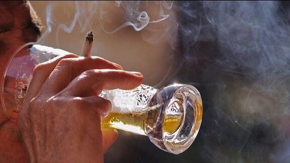 Ein Mann trinkt Bier aus einem Glas und hält dabei eine Zigarette zwischen den Fingern.)