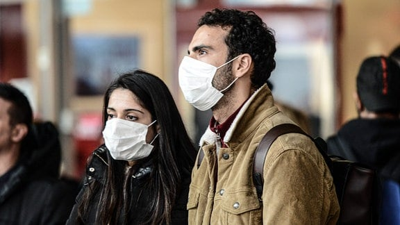 Eine Frau und ein Mann mit weißen Atemschutzmasken.
