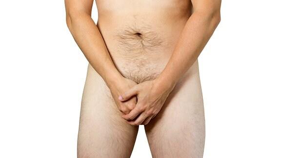 Ein nackter Mann hält sich die Hände vors Geschlechtsteil.