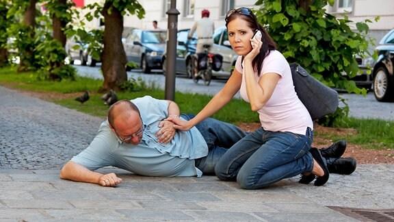 Eine Frau kniet neben einem Mann, der einen Herzinfarkt erlitten hat, und ruft über ihr Mobiltelefon Hilfe.