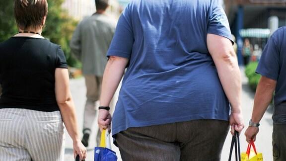 Zwei übergewichtige Frauen laufen in einer Fußgängerzone entlang.