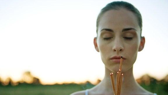 Eine junge Frau hält sich Räucherstäbchen unter die Nase