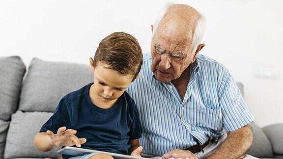 Ein alter Mann schaut mit seinem Enkel auf ein Tablett.