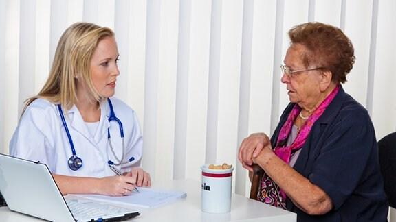 Eine junge Ärztin sitzt mit einer älteren Frau an einem weißen Tisch, auf dem ein Laptop steht, und unterhält sich mit ihr.