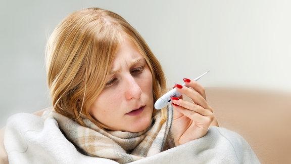 Eine junge Frau sitzt, in Decken eingewickelt, auf einem Stuhl und liest von einem Fieberthermometer die Temperatur ab.