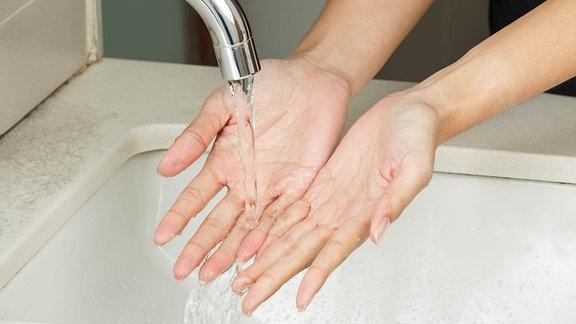 Hände kühlen unter laufendem Wasserhahn