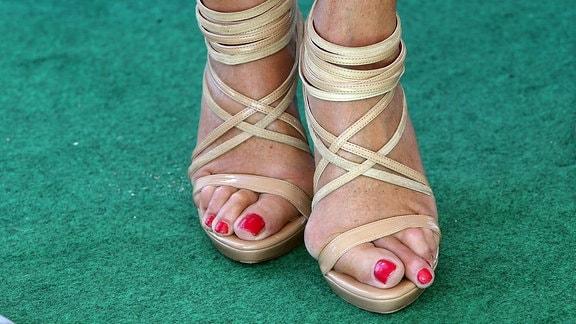 Frauenfüße mit Ballenzehen in Sandaletten