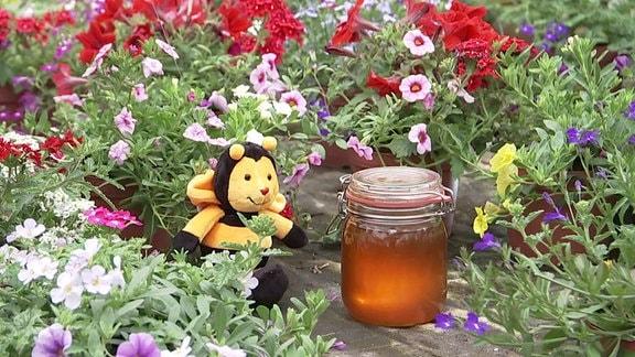 Eine Stofftier-Biene sitzt inmitten von Blumen, neben ihr ein Glas Honig.