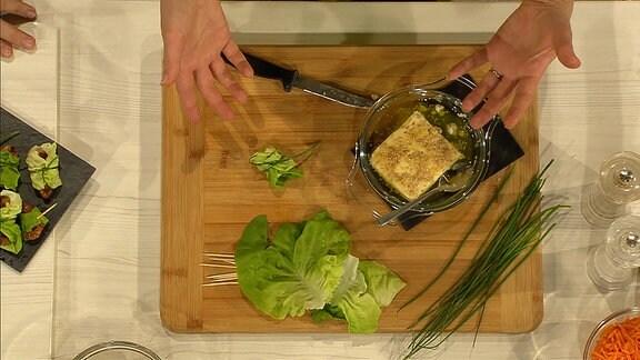 Ein Tablett von oben, auf dem Salatblätter, Schnittlauch und Feta liegen.