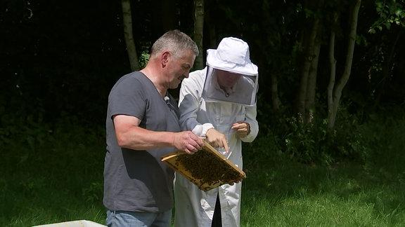 Zwei Männer neben einem Bienenstock.