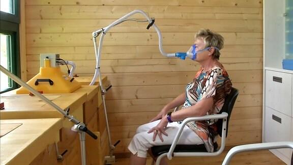 Eine Frau inhaliert an einem Inhalationsgerät.