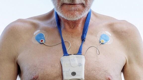 Mann mit mobilem EKG vor der Brust