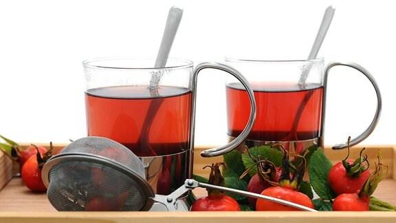 Zwei Gläser mit Hagebuttentee und Hagebutten auf einem Holztablett