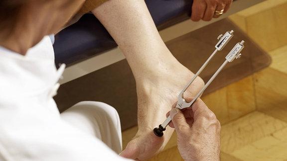 Ein Arzt untersucht mit einer Stimmgabel den Fuß eines Patienten.