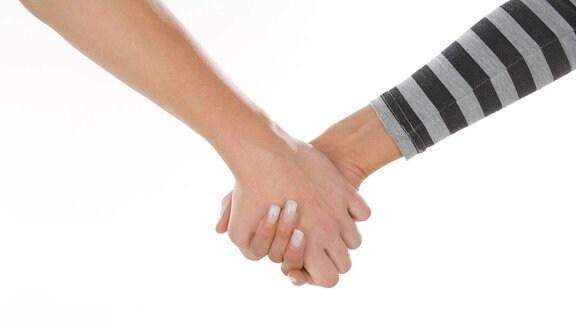 Junges Paar hält sich an der Hand