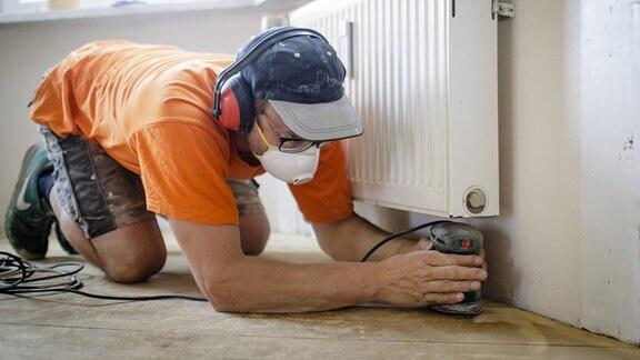 Ein Handwerker bearbeitet Holzdielen mit einer Schleifmaschine in einer Altbauwohnung.