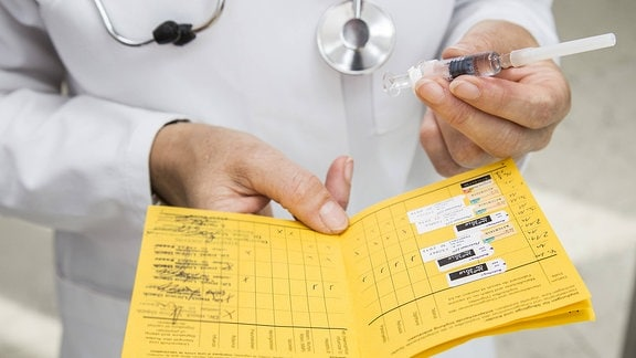Ein Arzt hält in der einen Hand einen aufgeschlagenen Impfausweis und in der anderen eine Impfspritze