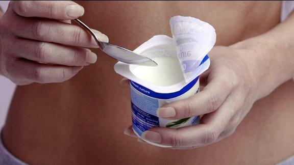 Eine Frau hält einen Joghurtbecher vor ihrem Bauch.