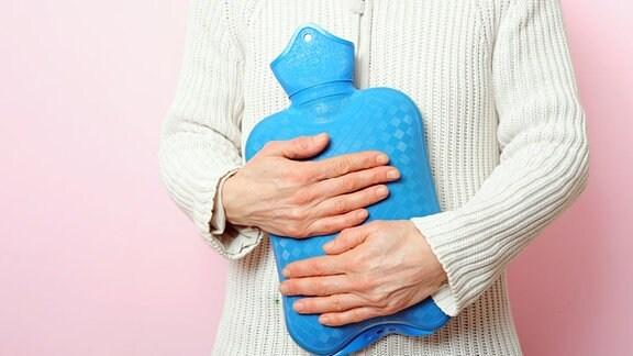 eine ältere Frau in einer weißen Strickjacke hält sich eine blaue Wärmflasche vor den Bauch
