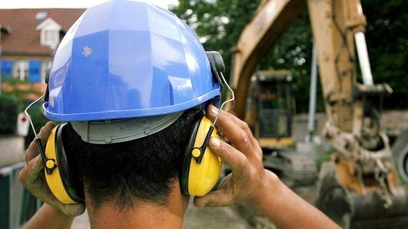 Ein von hinten zu sehender Bauarbeiter, der einen Bauhelm und einen Gehörschutz trägt, steht vor einem Kran.