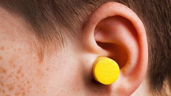 Ein gelber Ohrstöpsel steckt in einem Ohr.
