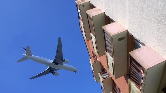 Ein Verkehrsflugzeug fliegt in geringer Höhe über ein Wohnhaus.