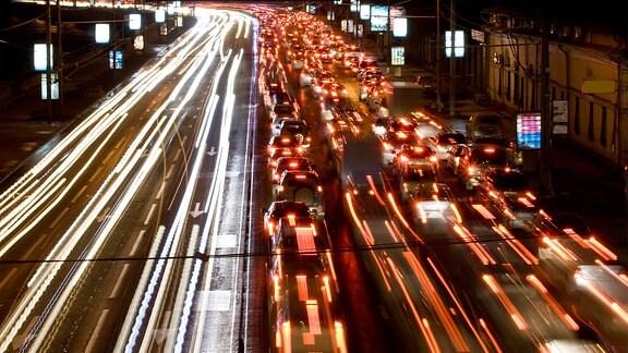 Lichtspuren von fahrenden Autos auf einer nächtlichen Straße.