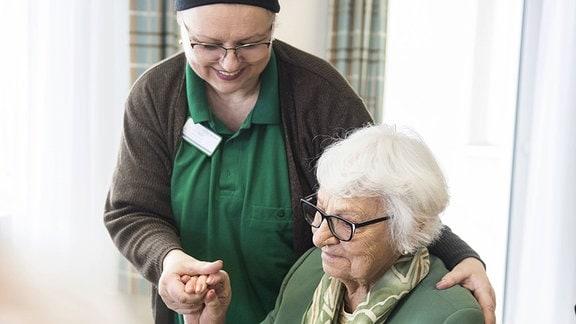 Lächelnde Pflegerin bei einer älteren Dame im Rollstuhl