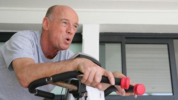 Ein Rentner sitzt in einem Fitnessstudio an einem Ergometer