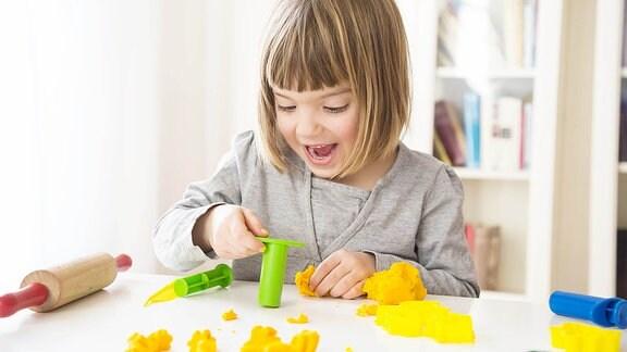 Ein kleines Mädchen spielt mit Knete.