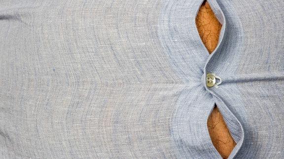 Dicker Bauch mit gespanntem Hemd eines Mannes mit Übergewicht