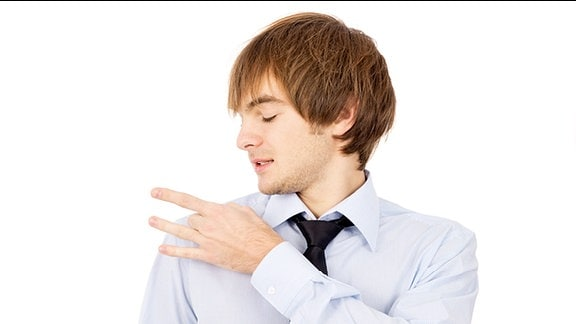 Ein junger Mann entfernt Schuppen von seiner Schulter.