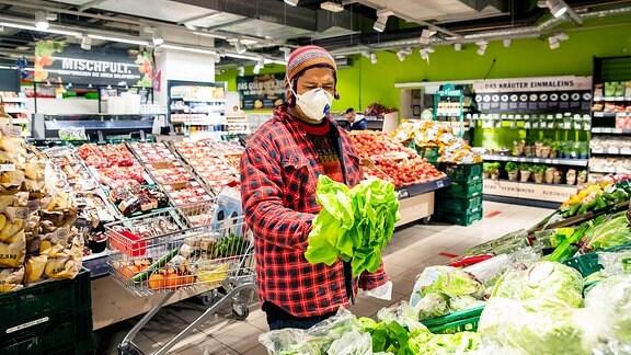 Ein Mann ist im Supermarkt mit Mundschutz einkaufen.