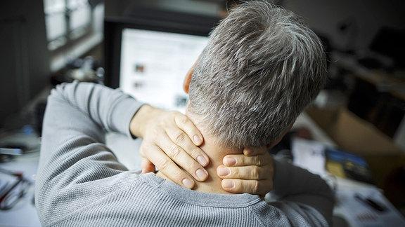 Ein Mann sitzt vor einem Laptop und hält sich vor Schmerzen den Nacken.