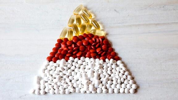Tabletten in den Farben gelb, rot und weiß sind farblich in Schichten getrennt zu einem Dreieck gelegt.