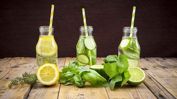 drei Glasflaschen mit aromatisiertem Wasser