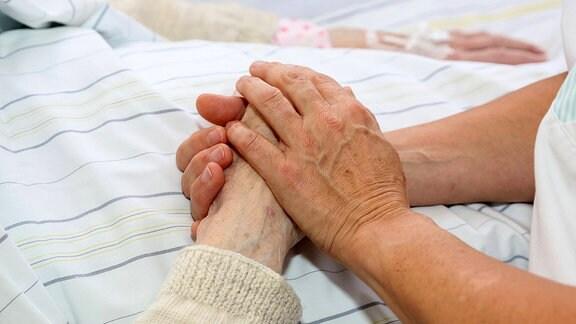Eine Krankenschwester kümmert sich um eine Patientin und gibt ihr Zuwendung indem sie ihre Hand hält.