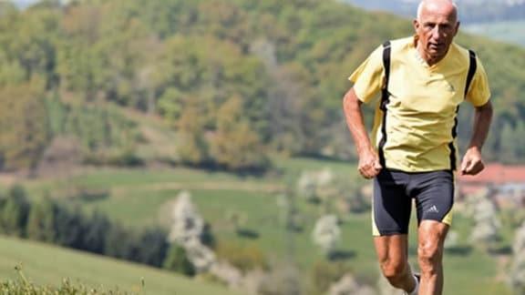 Ein Rentner joggt auf blühenden Bergwiesen.