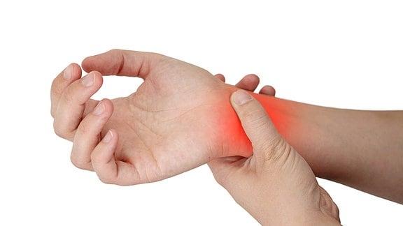 Eine weibliche Hand umfasst das Gelenk der anderen Hand. Die Stelle ist rot eingefärbt.