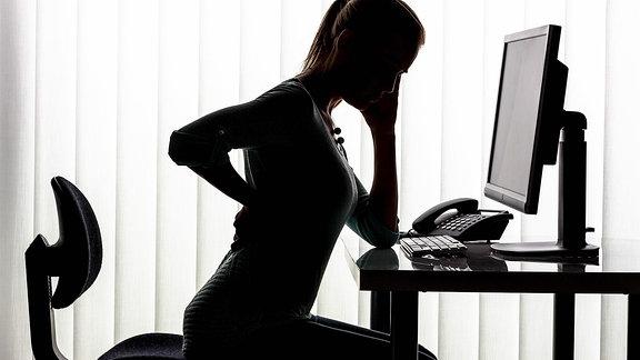 Silhouette einer Frau, die in einem Büro am Schreibtisch sitzt und sich an den Rücken fasst.