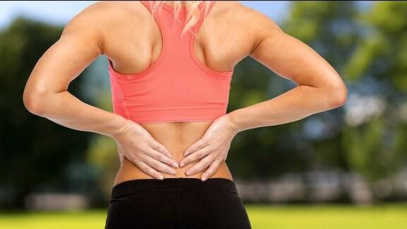 Eine Frau in Sportkleidung hält sich den Rücken