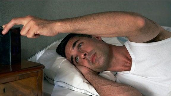 ein Mann liegt ruhelos in seinem Bett und sieht auf seinen Wecker