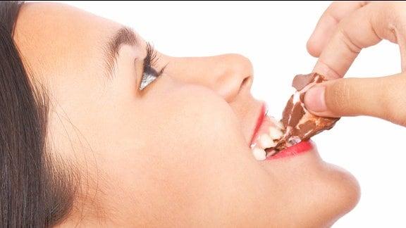 Eine Frau isst genussvoll etwas Süßes.