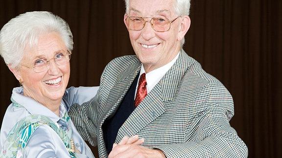Ein älterer Mann und eine ältere Frau lächelnd in Tanzstellung