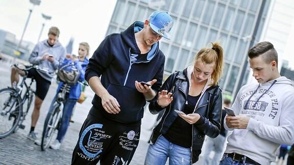 Junge Menschen stehen zusammen und sehen auf ihr Smartphone
