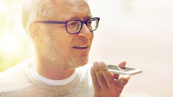 Senior benutz Sprachsteuerung seines Smartphones