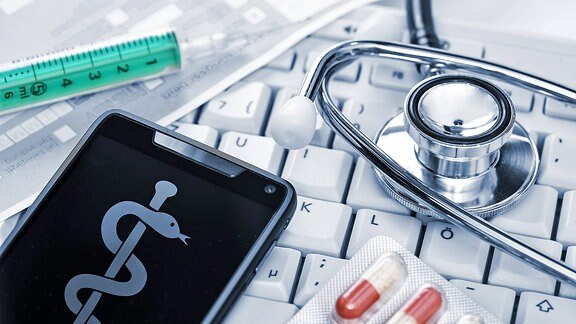 Ein Stethoskop, ein Smartphone, eine Spritze und Medikamente liegen auf einer Computertastatur.