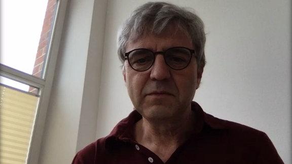 Ein Arzt führt eine Videosprechstunde mit einer Patientin durch; Screenshot vom Handy der Patientin