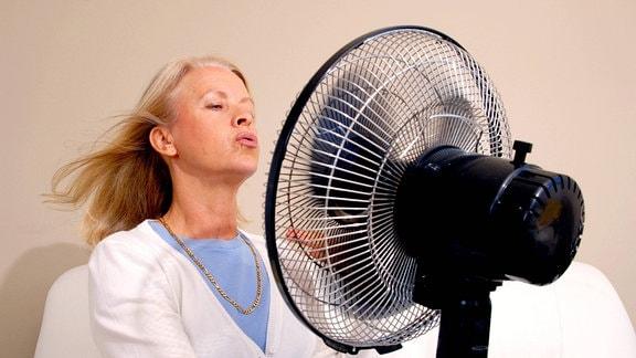 Frau in den Wechseljahren vor Ventilator